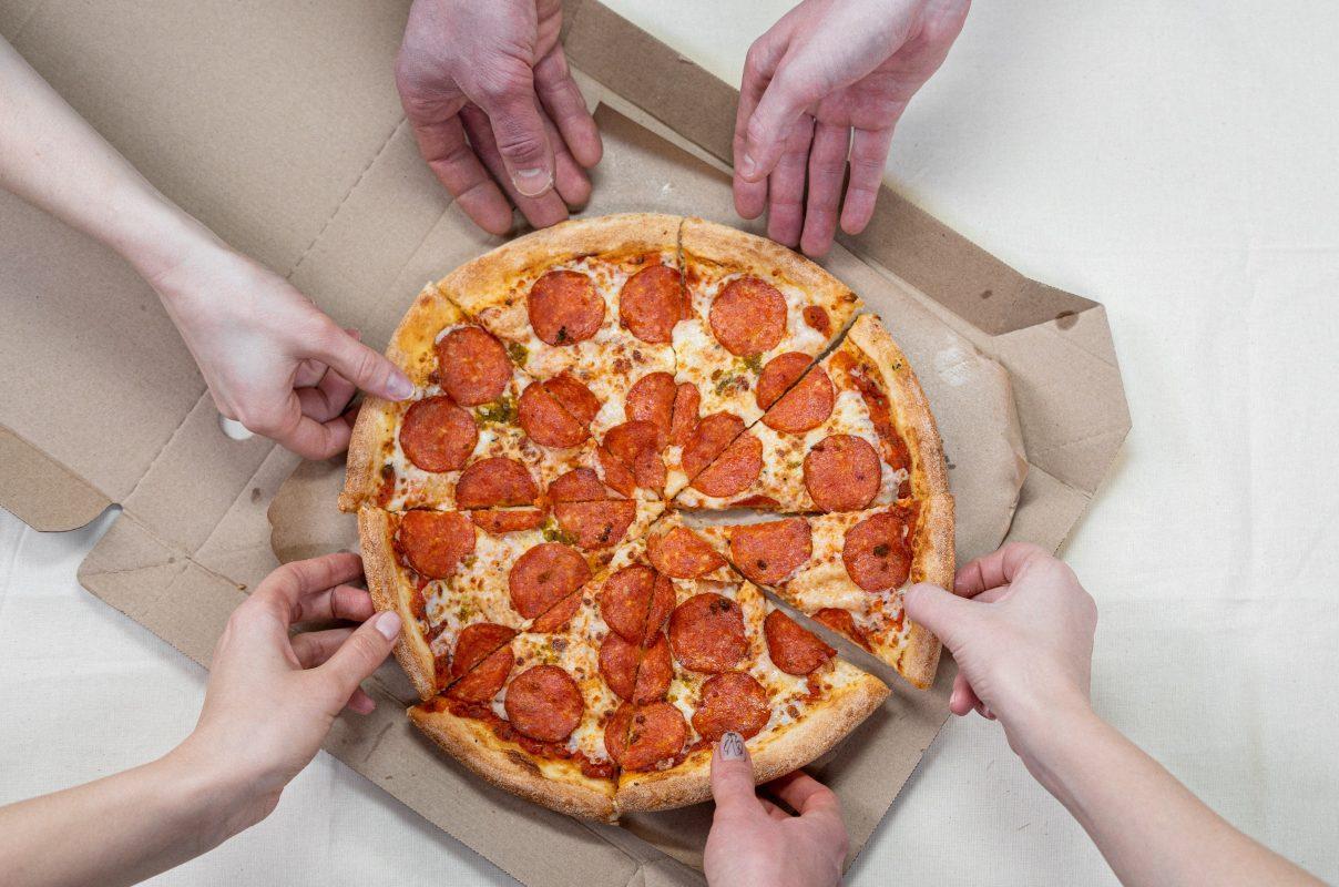 Sechs Hände greifen nach einer Pizza
