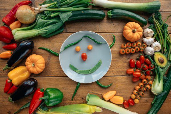 Verschiedene Gemüse um ein Gemüse-Smiley garniert.